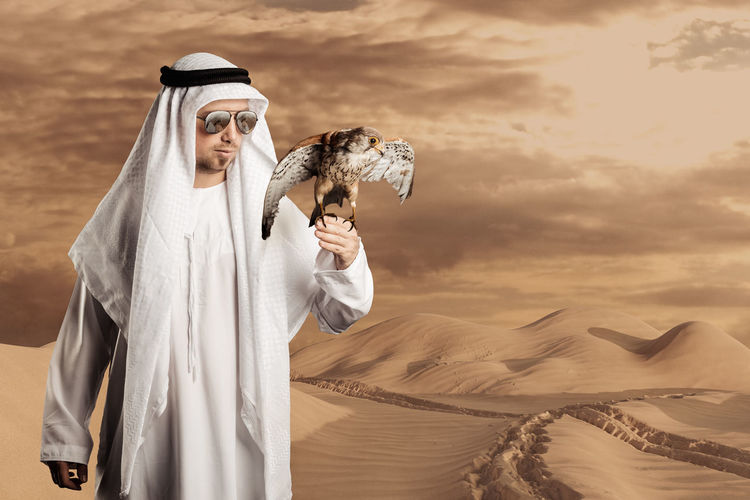 sheik with sunglasses holding a falcon in front of desert hills and footsteps Desert Path Pathway Falcon Man Male Sheikh Proud Holding Desert Sand Sand Dune Young Adult Copy Space Standing Nature Arabian Arabia Arabic Arabian Culture Arabic Culture Bird Birds Of Prey Keffiyeh Dunes Hills Clothing Traditional Tradition Watching Lifestyle Outdoors Preparing Ready To Fly