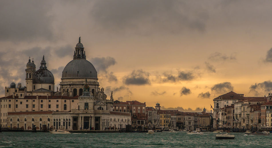 Grand canal amidst santa maria della salute and building against cloudy sky