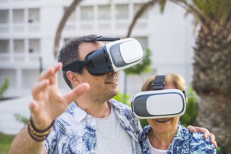 technology concept for no young people middle age and mature man and woman enjoying the outdoor leisure activity with virtual reality 3d playful lifestyle together laughing and smiling Virtual Reality Simulator Technology Wireless Technology Real People Leisure Activity Connection Headshot Young Adult Gesturing Communication Lifestyles Front View Futuristic Young Men People Glasses Adult Wearable Computer Men Portrait Cyberspace 3-d Glasses Outdoors Hands-free Device Family Mother Son Senior Adult Elderly Woman Retired Females Caucasian Casual Clothing Enjoying Life Emotion Surprise