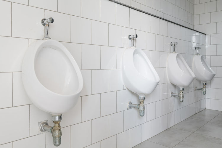 Toilet bowl in a modern bathroom Bathroom Clean Convenience Domestic Bathroom Domestic Room Flooring Home Hygiene In A Row Indoors  No People Public Building Public Restroom Sink Tile Tiled Floor Toilet Urinal Wall - Building Feature White Color