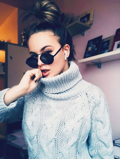 Portrait of fashionable teenage girl wearing sunglasses and sweater standing at home