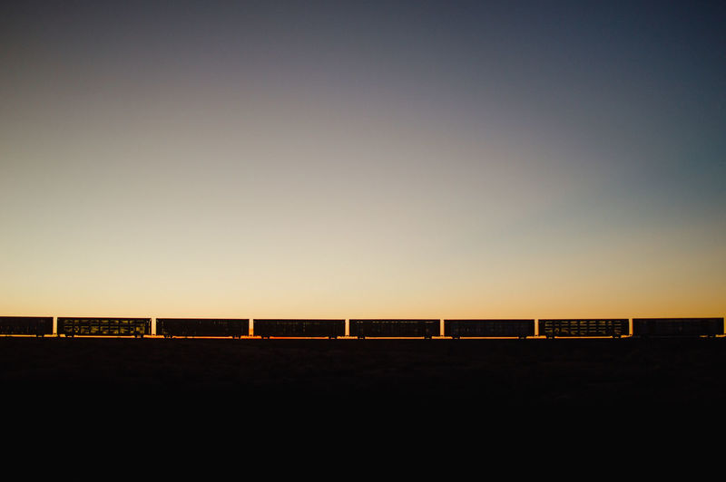 Silhouette Freight Train Against Clear Sky During Sunset