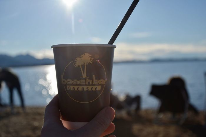 Coffee Real People Sunlight Chiemsee Bavaria Bavarian Alps Lake Human Hand Holding Beach Beach Bar Text Leisure Activity One Person Lifestyles Sun Nature Outdoors Day Human Body Part Sky Close-up Sand Coffee Cup Cup EyeEmNewHere Live For The Story