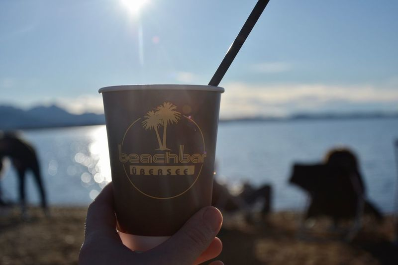Coffee Real People Sunlight Chiemsee Bavaria Bavarian Alps Lake Human Hand Holding Beach Beach Bar Text Leisure Activity One Person Lifestyles Sun Nature Outdoors Day Human Body Part Sky Close-up Sand Coffee Cup Cup EyeEmNewHere Live For The Story EyeEmNewHere