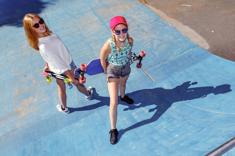 High Angle Portrait Of Friends With Skateboards In City During Sunny Day