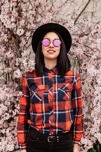 Portrait of woman wearing sunglasses standing against cherry blossom