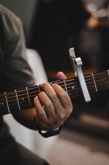 Cropped image of man playing guitar
