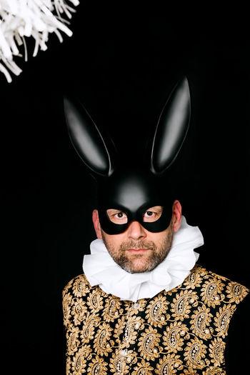 Portrait of man wearing hat against black background