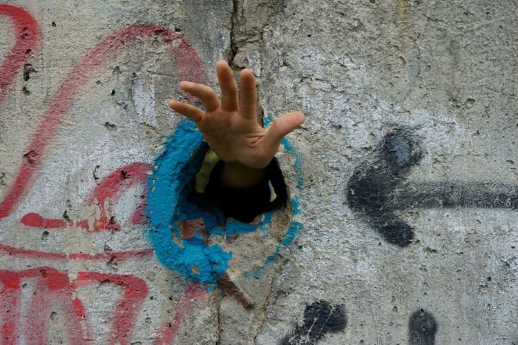 Hand In Hole On Concrete Wall