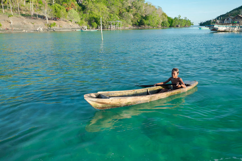 Wonderful portrait of Sea gypsy kid,mom on a wooden canoe with crystal clear water in Sabah, Malaysia. Amazing seascape with clear sky and beautiful island background. Amazing Place Asian  Beauty In Nature Blue Blue Sky Borneo Island Canoe Clear Water Clear Water Beach Colorful Corals Day Kids Life Is A Beach Malaysia People Poor Kids Poor People  Seagypsy Seascape Tranquil Scene Tranquility Water Waterfront Wooden Canoe