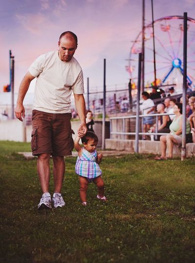 Father and daughter holding hands while walking in amusement park
