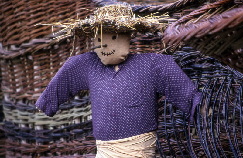 Close-up of scarecrow by whicker baskets
