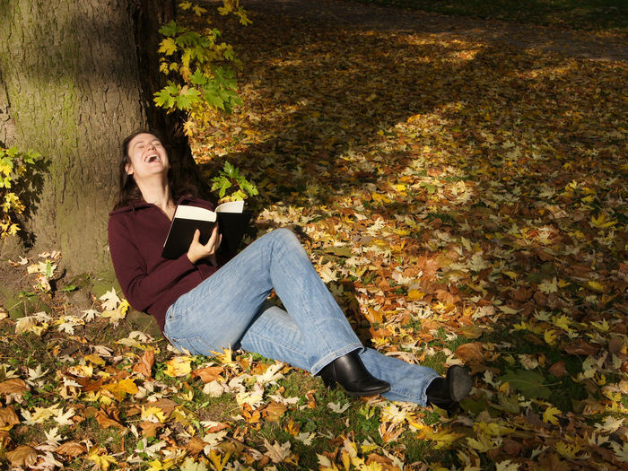 Full length of woman laughing while holding book by tree at park during autumn