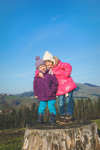 Two young girls standing on tree trunk on a cold winter day Lifestyle Tree Trunk Winter Clothing Beauty In Nature Blue Childhood Clear Sky Day Elementary Age Front View Full Length Girls Happiness Leisure Activity Looking At Camera Nature Outdoors Portrait Real People Sky Smiling Standing Winter Day