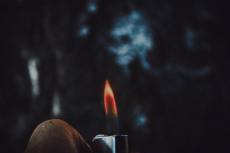 Close-up of human hand holding burning cigarette lighter at dusk