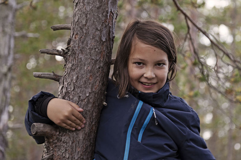 Portrait of a smiling girl on tree trunk