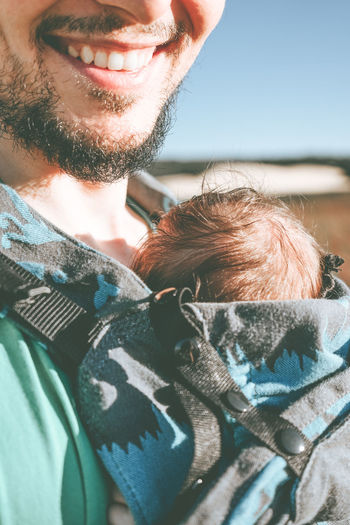 Midsection of father holding baby standing outdoors