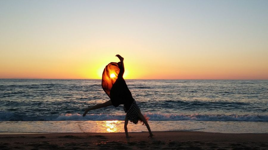 Teenage girl doing cartwheel at beach against sky during sunset