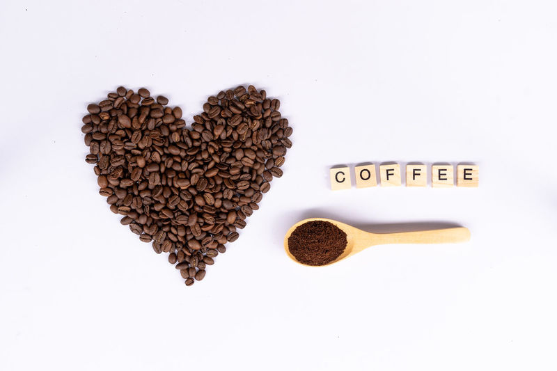top view coffee bean in shape of heart with wooden spoon and coffee text Love Lover Brown Close-up Coffee Coffee - Drink Coffee Beans Communication Crushed Beans Directly Above Emotion Food Food And Drink Freshness Heart Beat Heart Shape Indoors  Love No People Positive Emotion Roasted Coffee Bean Studio Shot Text Top View Western Script White Background Wooden Spoon