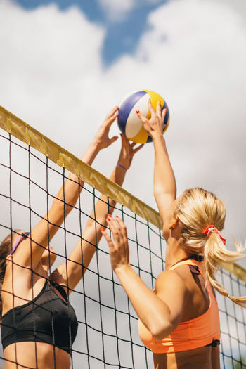 Low Angle View Of Women Playing Beach Volleyball Against Sky