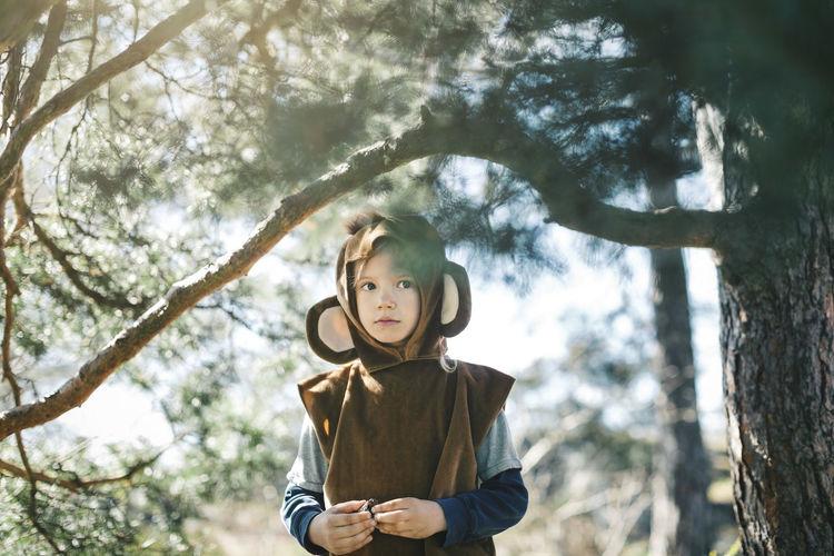 Low angle portrait of boy wearing hat on tree trunk
