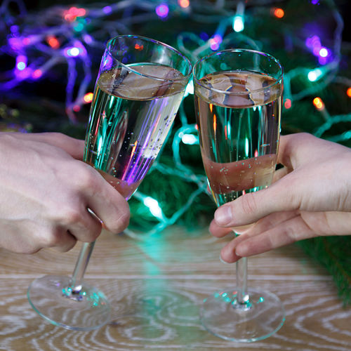 Celebratory Toast Party - Social Event Togetherness Christmas Drinking Couple - Relationship Holding Adults Only Celebration Human Body Part Two People Human Hand Alcohol Drinks Champagne Glass Cheers Cheers To Life Christmas Lights Bubbly Mery Christmas Beverage Champagne Wine Decor Bokeh Night Lights