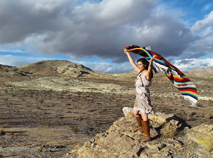 Young woman holding shawl while standing on rock formations at mojave desert