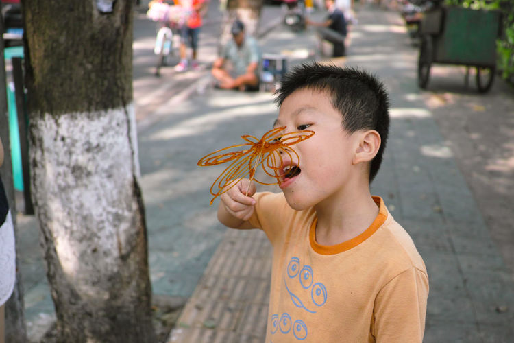 Cute boy eating candy outdoors