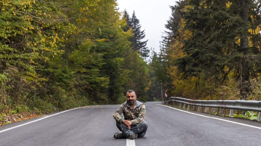 Full length of man sitting on road amidst forest