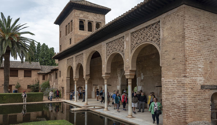 GRANADA, SPAIN - October 11, 2018: The famous Alhambra in Granada, Spain. It is a palace and fortress complex located in Granada. Granada SPAIN Alhambra Alhambra De Granada  Architecture Arabic Style Ancient Architecture Mosque Architecture Interior Design Built Structure Group Of People Building Exterior Real People Arch The Past History Day Men Tourism Lifestyles Crowd Large Group Of People Palm Tree Outdoors Architectural Column