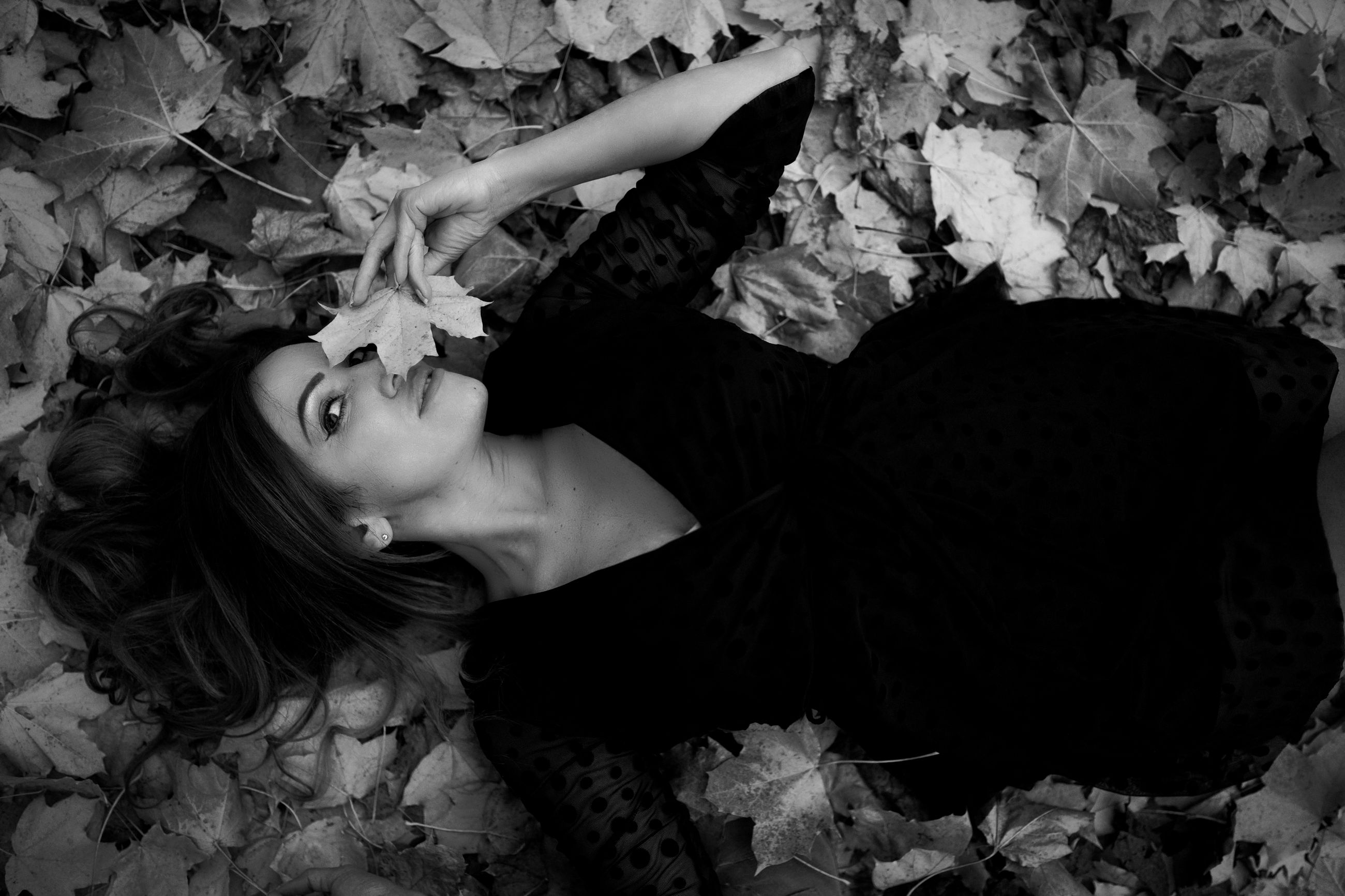 one person, black, leaf, plant part, black and white, women, lying down, adult, young adult, portrait, monochrome photography, monochrome, darkness, fashion, hairstyle, nature, high angle view, white, female, looking at camera, lifestyles, long hair, portrait photography, autumn, flower, person, lying on back, relaxation, plant, leisure activity, falling, emotion, photo shoot, indoors, dress, contemplation, clothing
