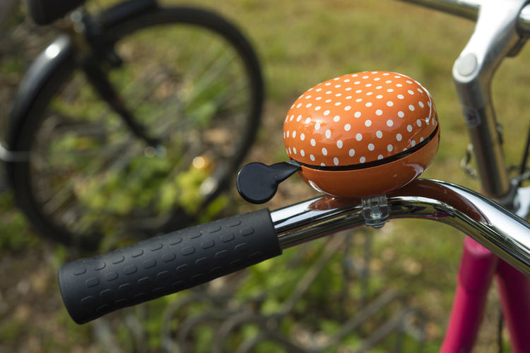 Detail of an orange bicycle ring bell outdoors Backgrounds Beautiful Bell Bike Detail Handlebar Lifestyles Metal Orange Ring Ring Bell Ringbell Sport Transportation Vintage