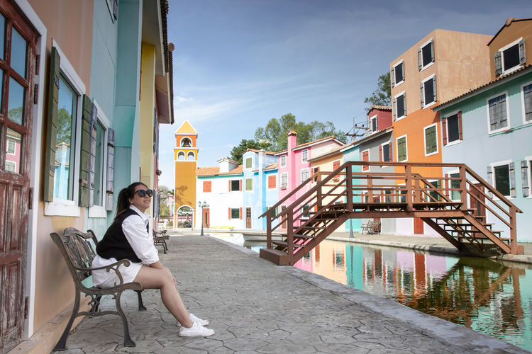 Woman sitting on chair by canal against buildings