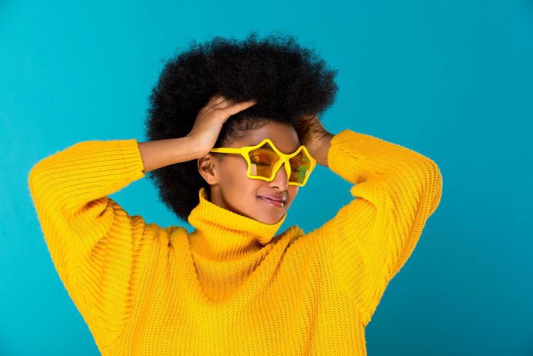 Smiling young woman with hand in hair wearing sunglasses against blue background
