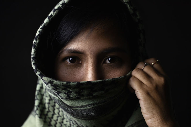 Close-up portrait of young woman wearing scarf against black background