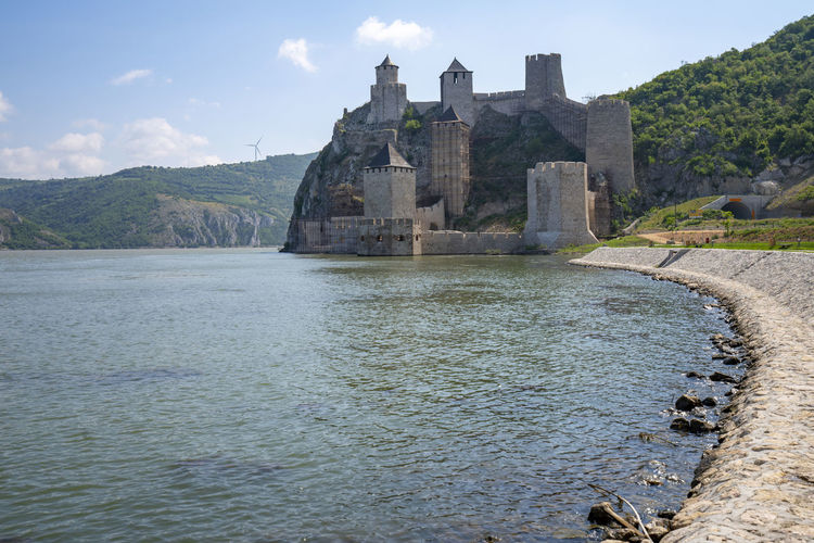 View of castle by river against sky