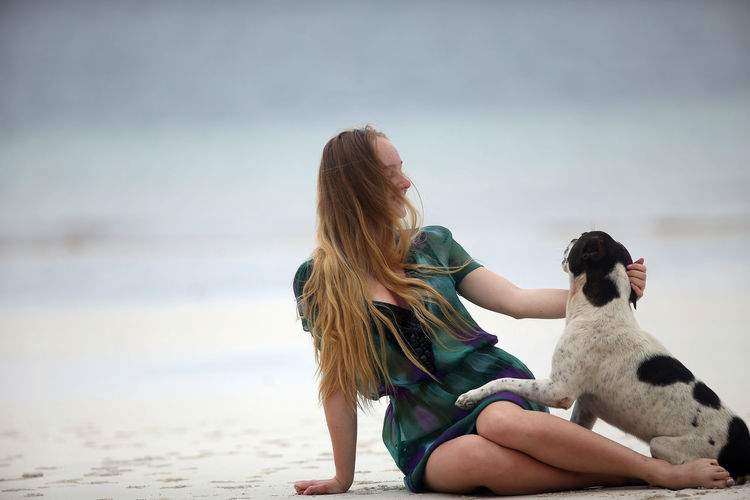 Full length of woman with dog sitting on beach
