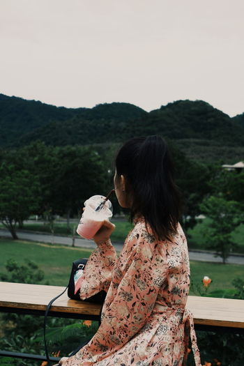 Side view of woman drinking milkshake outdoors