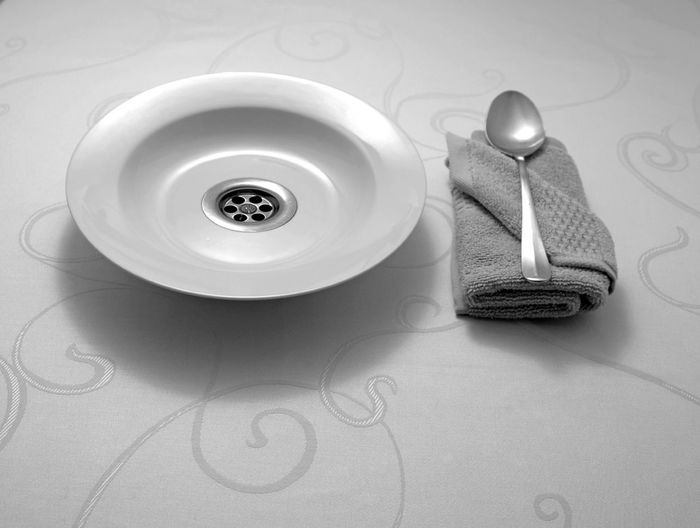 High angle view of antique plate by spoon and dish towel on table