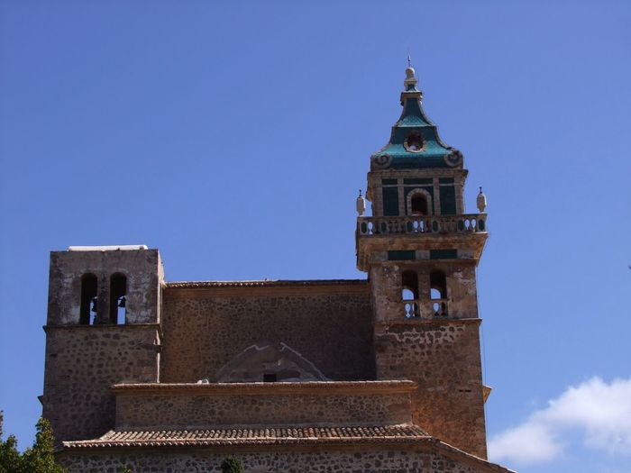 Bell Tower & Tower, Valldemossa Monastery Church Composition Mallorca Monastery SPAIN Two Towers Valldemossa Valldemossa Monestary Architectural Features Architecture Belltower Blue Sky Building Exterior Building Facade Built Structure History Low Angle View No People Outdoor Photography Place Of Worship Religion Religion Architecture Stone Building Tiled Roof  Tower