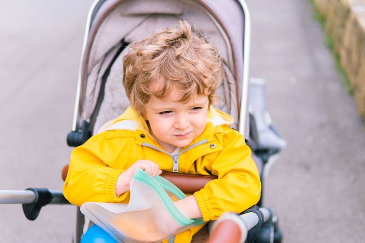 Cute boy sitting with food in baby carriage outdoors
