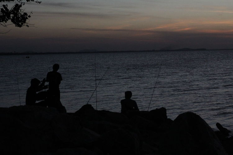 Silhouette people fishing in sea against sunset sky