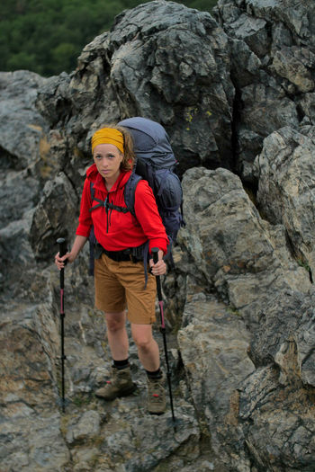 portrait of a caucasian female hiker standing on the rock with backpack Alpine Backpacking Boots Camping Expedition Freedom Hiking Nature Travel Trekking Woman Youth Activity Adult Adventure Backpack Caucasian Climbing Extreme Sports Female Front View Full Length Girl Helmet Hobby Leisure Activity Mountain Nature One Person Outdoors People Protection Rock Rock - Object Rock Climbing Safety Safety Harness Solid Sport Walking