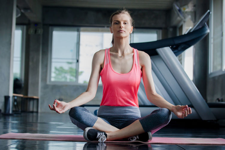 Portrait of woman mediating while sitting in gym