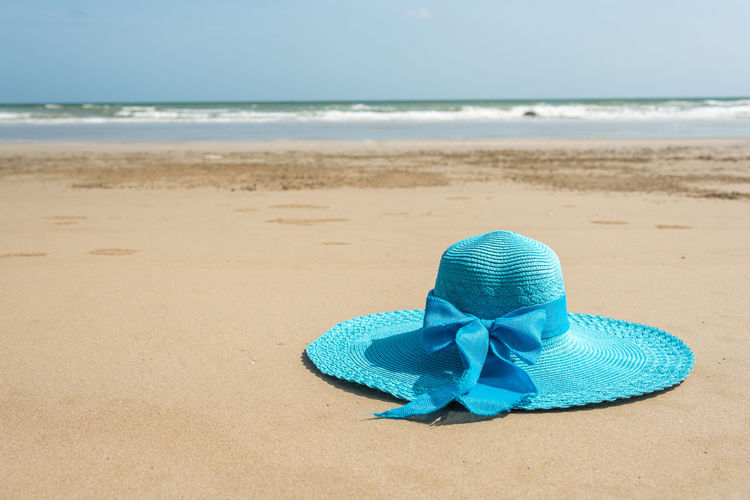 Blue Hat On Sand At Beach Against Sky