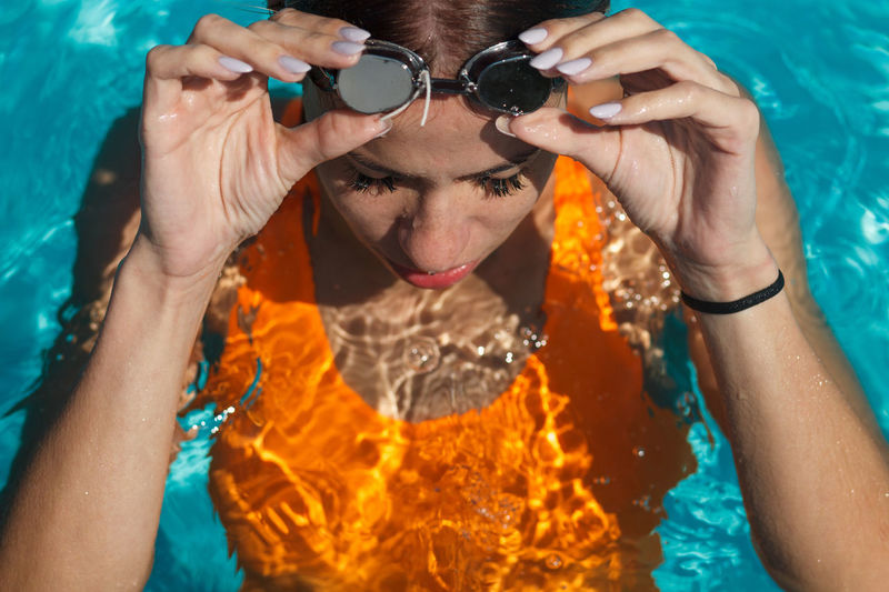 Portrait of man holding sunglasses in swimming pool