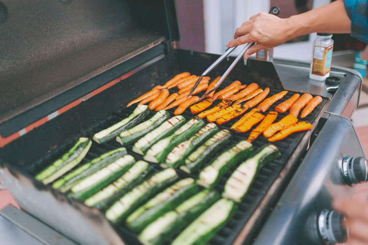Cropped hand of person preparing food on barbecue grill