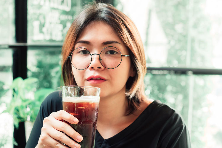 Portrait of young woman holding drink in cafe