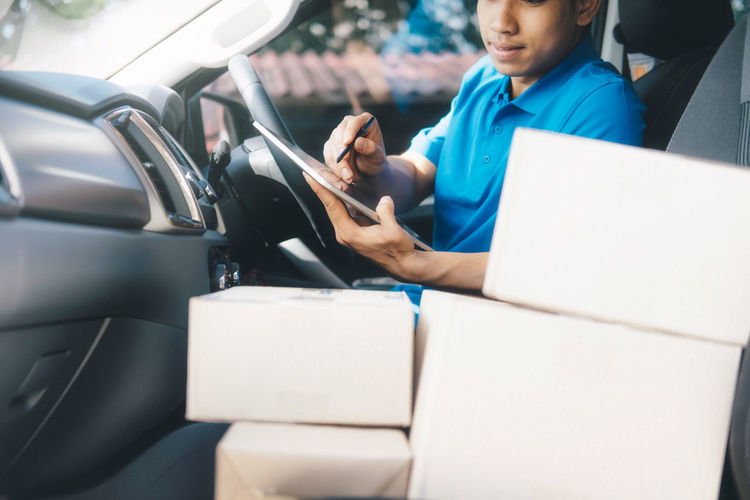 Delivery man using digital tablet while sitting in car