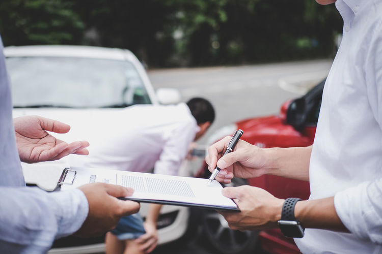 Midsection of man signing document with salesperson against cars